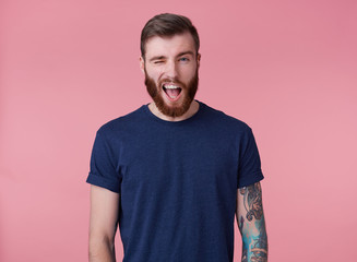 Young attractive red-bearded guy with blue eyes, wearing a blue t-shirt, looking at the camera and winking, look cool isolated over pink background.
