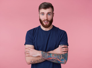 Portrait of young happy amazed attractive red-bearded young guy with crossed arms, wearing a blue t-shirt, looking at the camera with wide open mouth in surprise isolated over pink background.