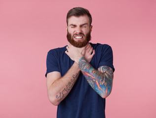 Portrait of young red-bearded unhappy man, can't find a way out, displeased, trying to strangle himself, scowl and grin isolated over pink background.