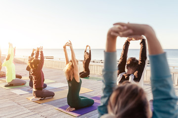 Yoga class at sea beach in evening. Group of people doing yoga poses with calm relax emotion at wooden fitness terrace with young instructor. Meditation pose,Wellness and Healthy balance lifestyle.