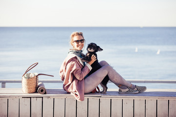 Beautiful young woman playing with her little west highland black terrier at the wooden terrace on the beach outdoors. Lifestyle portrait. Happy joy with pet, friendship of human and animal