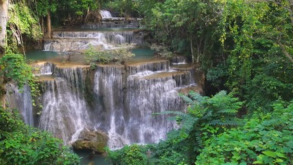 Wall Mural - Waterfall flow standing with forest enviroment high angle view in thailand called Huay or Huai mae khamin in Kanchanaburi Provience, Thailand., Panning Left, Panning.
