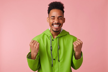 Joyful young african american handsome guy stands over pink background, clenched his fists, broadly smiling and absolutely happy - he won the lottery!