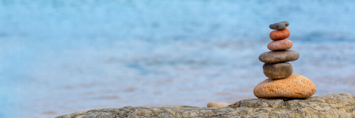 Stores à enrouleur Zen Pile of pebbles on a beach, panoramic blue water background, balanced stack of stone with copy space, zen web banner