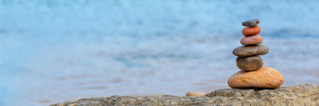 Pile of pebbles on a beach, panoramic blue water background, balanced stack of stone with copy space, zen web banner