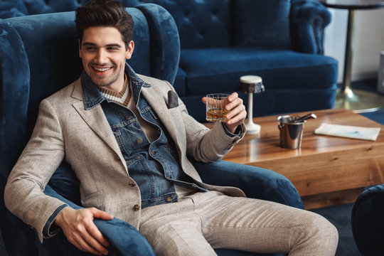 Young business man sitting in chair indoors in office drinking alcohol.