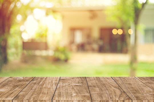 wooden table space with green home backyard view blur background for advertising template