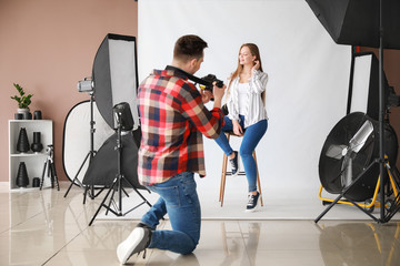 Young male photographer working with model in studio