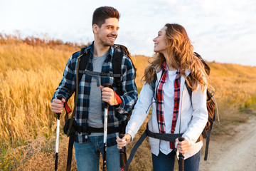 Cheerful young couple carrying backpacks hiking together