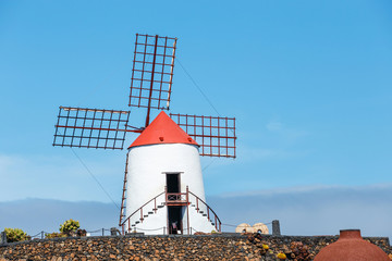 Windmill on blue sky background in cactus garden, Guatiza village, Lanzarote, Canary islands
