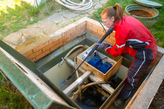 plumber cleans a septic tank using car wash high pressure. Purification station. Sewage treatment plant.