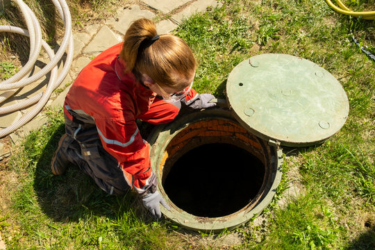 Girl plumber looks into an open draining manhole. top view. Service of the house individual sewerage.