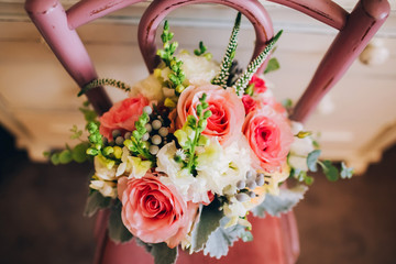 bouquet with pink roses on a pink chair. wildflowers.