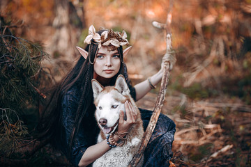 beautiful elf woman fabulous, fairy forest, famtasy young woman with long ears, long dark hair golden wreath crown on head with red dog like wolf Wall mural
