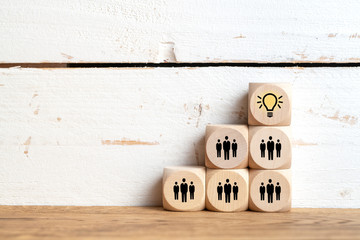 many people together having an idea symbolized by icons on cubes on wooden background