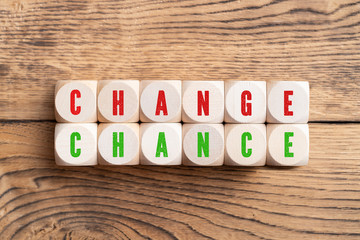 """twelve cubes with letters, showing the words """"change"""" and """"chance"""" on wooden background"""