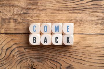 """Würfel mit Aufschrift """"Comeback"""" auf Holzhintergrund"""