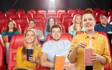 cinema, fast food and entertainment concept - smiling red haired teenage girl in checkered shirt eating popcorn from striped bucket over people in movie theater background