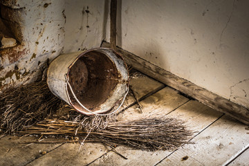 Old rusted bucket and broom in the corner of a abandoned old farm in Belarus, Chernobyl exclusion zone