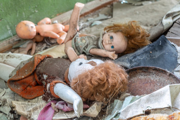 Dirty old dolls in an abandoned house in Chernobyl exclusion zone in Belarus