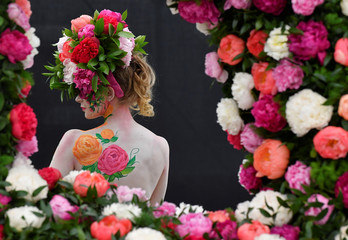 A model poses with body art and headwear made of Peonies at the RHS Chelsea Flower Show at the Royal Hospital Chelsea, London