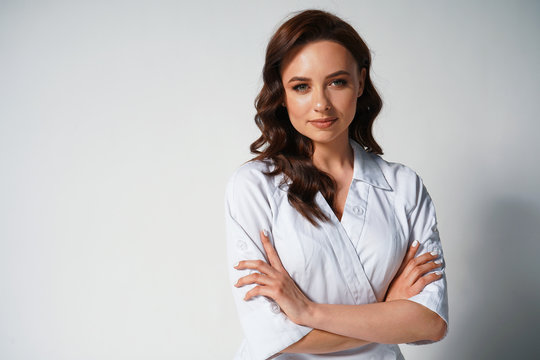 Portrait of attractive young female doctor in white medical jacket isolated on white background. Brunette woman cosmetologist smiling at the camera. Cross hands. Space for text. Healthcare concept