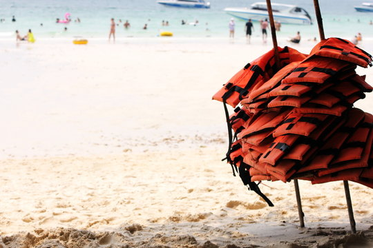 A lot of life jackets hanging on the beach. The concept of water safety.