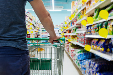 Closeup view of man's hand on shop trolley cart. Shopping with discount prices shelfes in grocery. Consumerism lifestyle.