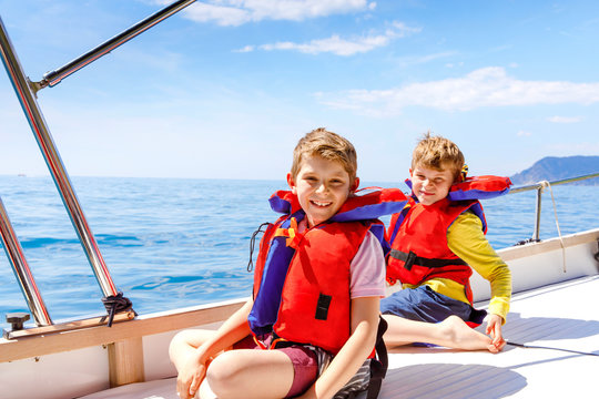 Two little kid boys, best friends enjoying sailing boat trip. Family vacations on ocean or sea on sunny day. Children smiling. Brothers, schoolchilden, siblings having fun on yacht.