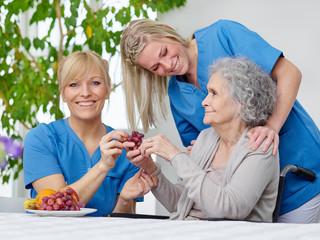 Seniorin mit Pflegerinnen
