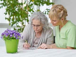 Seniorin löst Kreuzworträtzel