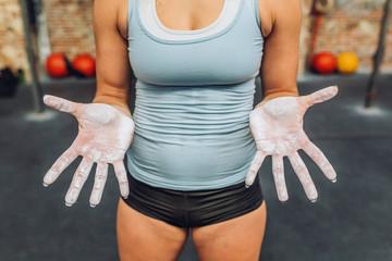 Crop sportswoman showing hands in chalk