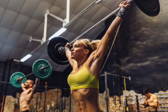 Strong people lifting barbells