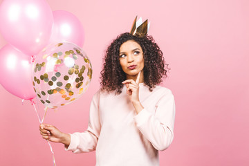 Celebration queen concept - close up portrait of happy cheerful young beautiful african american woman with pink t-shirt with colorful party balloons. Isolated against pink studio Background.