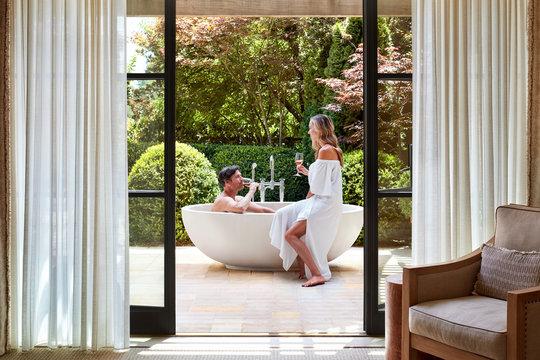 Couple in outdoor bathtub at luxury resort drinking Ros? wine