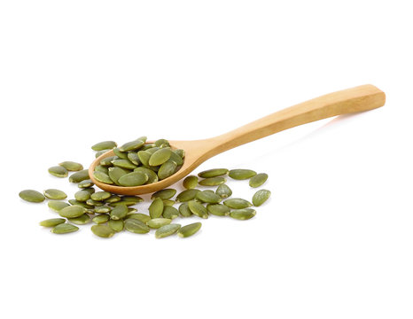 Pumpkin seeds in wooden spoon isolated on white background