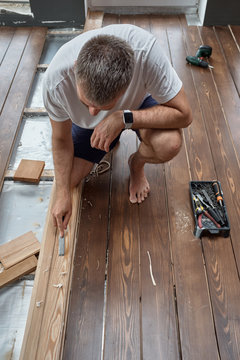 Man working with wood plank at home