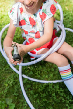Girl wrapped in hose on lawn