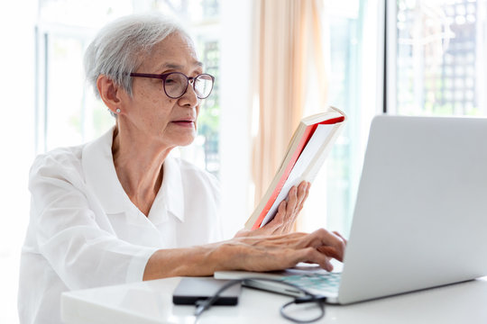 Asian senior woman working,surfing the internet with laptop computer in home,smiling elderly people with white hair sits in front of the computer and serf web-sites, technology and education concept