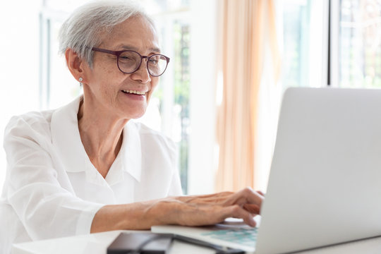 Happy asian senior woman working with laptop computer at table in home,smiling elderly people in glasses with white hair sits in front of the computer and serf web-sites, technology and people concept