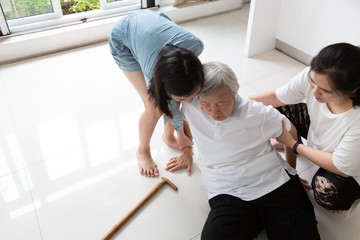 Asian elderly woman with walking stick on floor after falling down and caring woman assistant,sick senior or mother dizziness,faint,having a daughter,granddaughter to help and take care of her