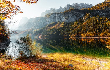 Amazing Alpine valley in Austrian Alps at Sunny day. Incredible Autumn Landscape with famous Lake Gosausee, and Dachstein glacier on background. Top Popular place for photographers and travelers.