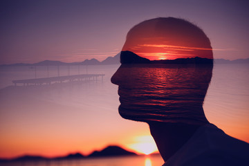 Silhouette of a young man in the background of the sunrise over the sea. Double exposure. Wall mural