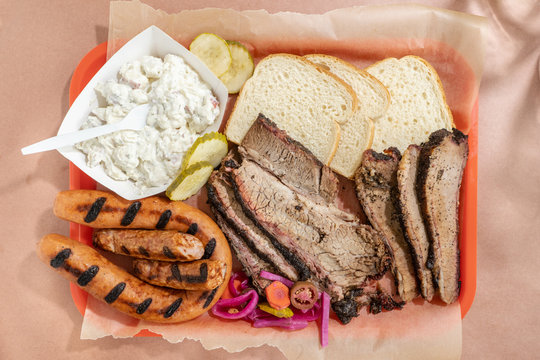 Texas barbecue plate with fatty and lean beef brisket, grilled pork sausage and Polish kielbasa, white bread, pickles, and potato salad.