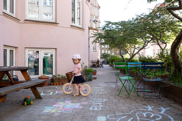 Little girl on bike looking at chalk drawings