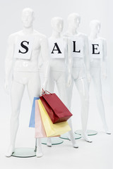 mannequins with sale lettering on papers and shopping bags on grey