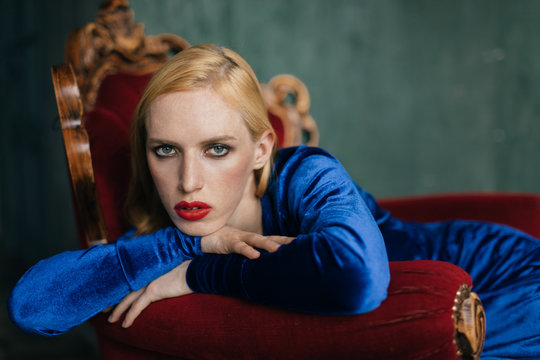 Portrait of androgynous young man in blue velvet dress