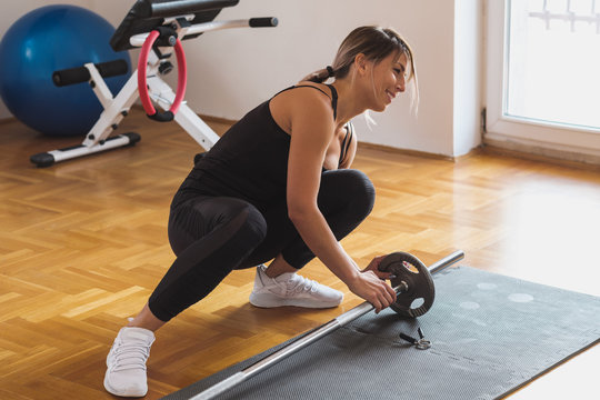 Woman Preparing For Weightlifting At The Gym