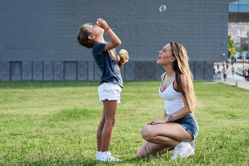 Blonde kid blowing tub of bubbles at park with sister.