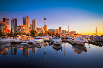 View of harbor in a yacht club at Toronto city during sunset with Canadian tower as background